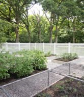 Photo of a white residential backyard garden fence.