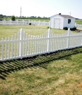 Photo of a white concave picket fence.