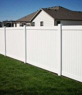 Photo of a residential white privacy fence.