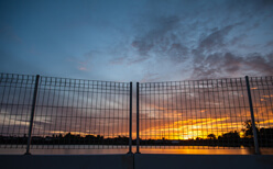 Photo of a durable commercial fence at night.
