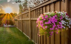 A wooden fence with flowers hanging on it, installed by a Fence Company in Springfield IL